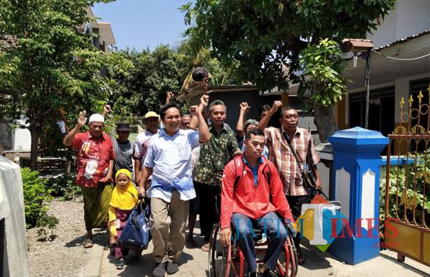 Tatok Hardiyanto pakai kursi roda peraih medali emas Para Games 2018 disambut warga yang ada di lingkungan rumahnya (Foto Heru Hartanto / SitubondoTIMES)