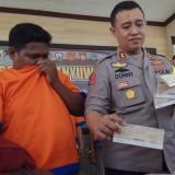 Kapolres Banyuwangi AKBP Donny Adityawarman menunjukkan bukti cek kosong di hadapan tersangka