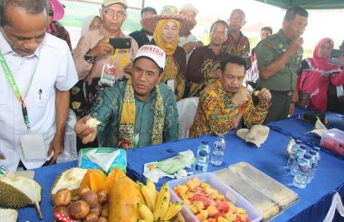 Menteri Pertanian Amran Sulaiman (mengenakan topi #Bekerja) saat mencicipi durian hasil pertanian Kota Malang di Kalimantan Selatan. (Foto: Humas Pemkot Malang for MalangTIMES)