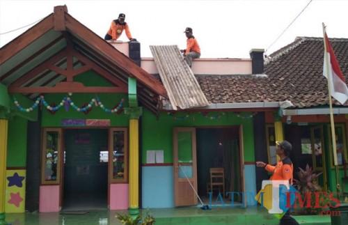 Petugas gabungan beserta warga saat membenahi bangunan rumah dan fasilitas umum berupa sekolah taman kanak-kanak pasca musibah melanda, Kecamatan Pakis (Foto : Ashaq Lupito / MalangTIMES)