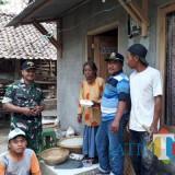 Kepala Dusun Sentong Baitul Aziz (pakai kaus bergaris) bersama babinsa dan anggota komunitas membagikan nasi kotak kepada warga. (foto : Moh. Ali Makrus / Jatim TIMES)
