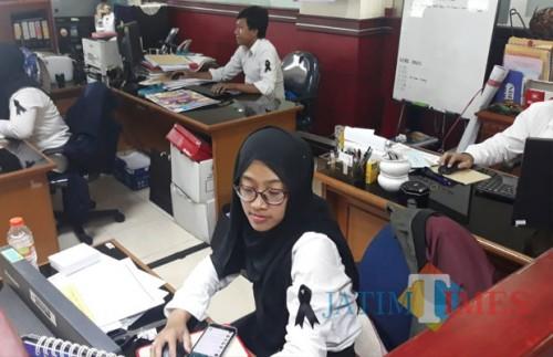 Para petugas pajak DJP Jawa Timur III Malang tengah melakukan aktivitas harian mengenakan seragam hitam putih dan pita hitam. (Foto: Nurlayla Ratri/MalangTIMES)