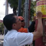 Kepala BP2D Kota Malang Ade Herawanto saat menandatangani stiker peringatan pada reklame yang belum melunasi pajak daerah. (Foto: Nurlayla Ratri/MalangTIMES)