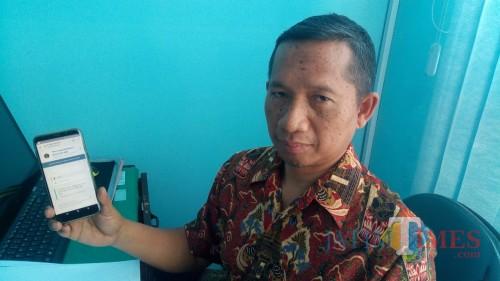 Kabid PIAK Dispendukcapil Pemkab Blitar Imam Maini menunjukkan cara pengurusan e-KTP melalui ponsel android.(Foto : Aunur Rofiq/BlitarTIMES)
