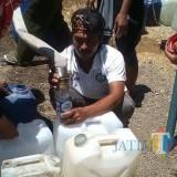 Salah satu relawan tampak merekayasa botol air mineral jadi torong agar air bisa masuk ke jurigen (Foto : Istimewa / TulungagungTIMES)