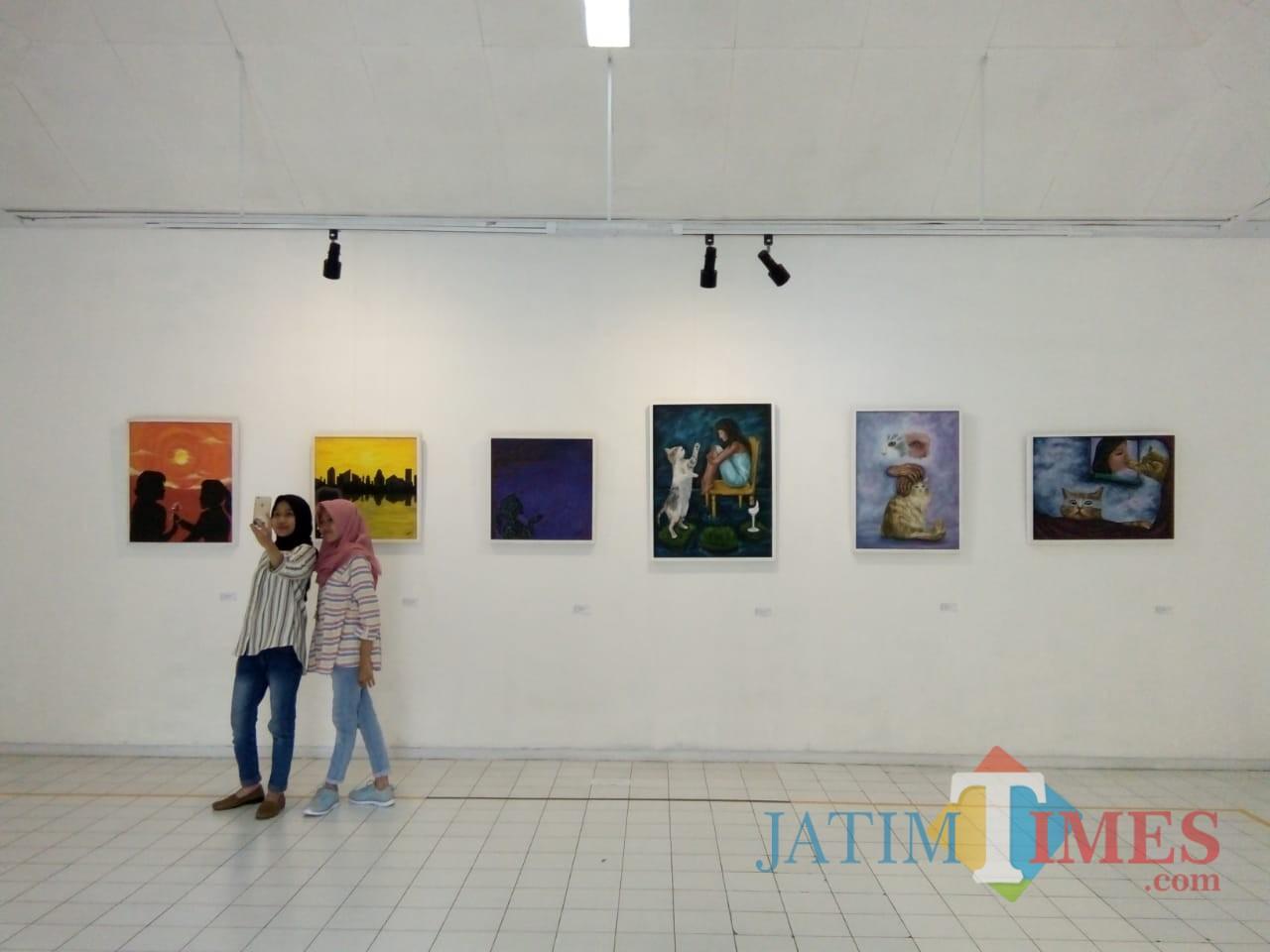 Pengunjung pameran tengah berfoto di depan lukisan hasil karya mahasiswa Universitas Negeri Malang di Gedung Dewan Kesenian Malang (Pipit Anggraeni)