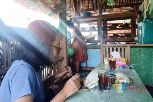 Pelanggan Rujak Syantik Tuplik saat menikmati rujak premium dari Desa Gesang Tempeh ini. (Foto: Pawitra/JatimTIMES)