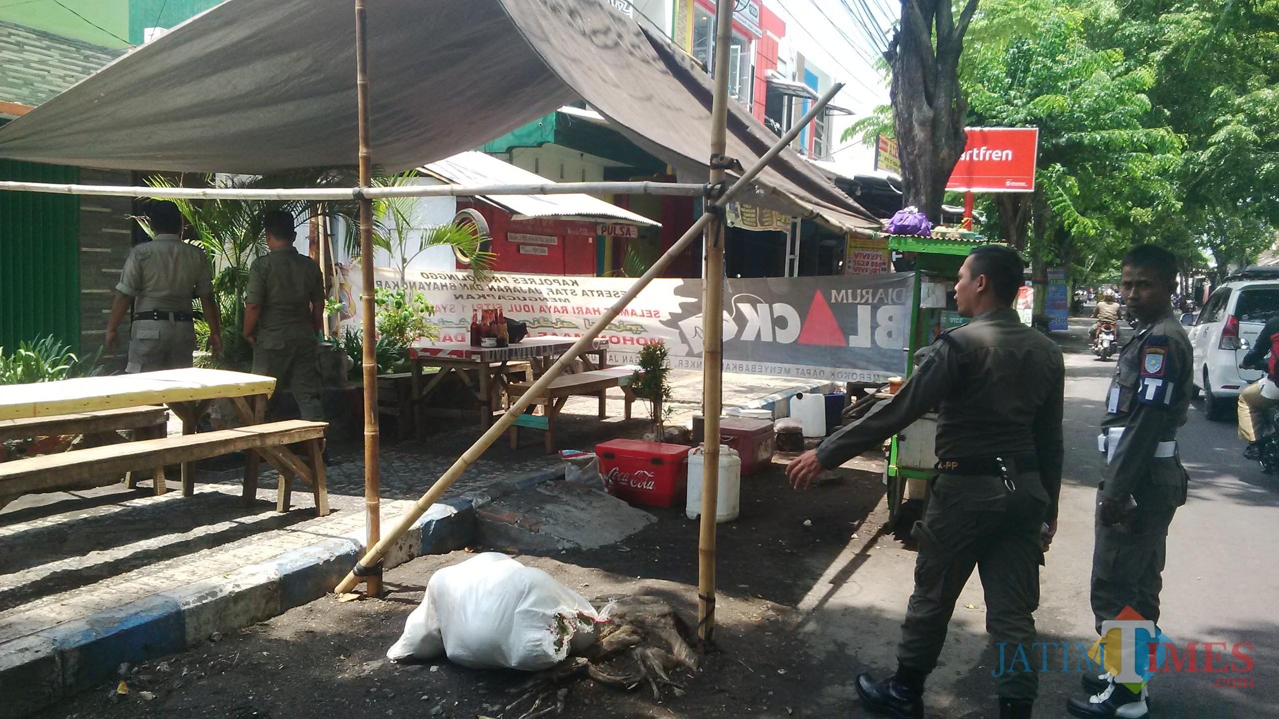 Petugas Satpol PP saat menertibkan PKL yang berjualan di Jalan Cokro (Agus Salam/Jatim YIMES)