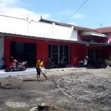 Warga membersihkan endapan air comberan yang meluber di halaman kompleks pertokoan dan kantor Peradi Banyuwangi.