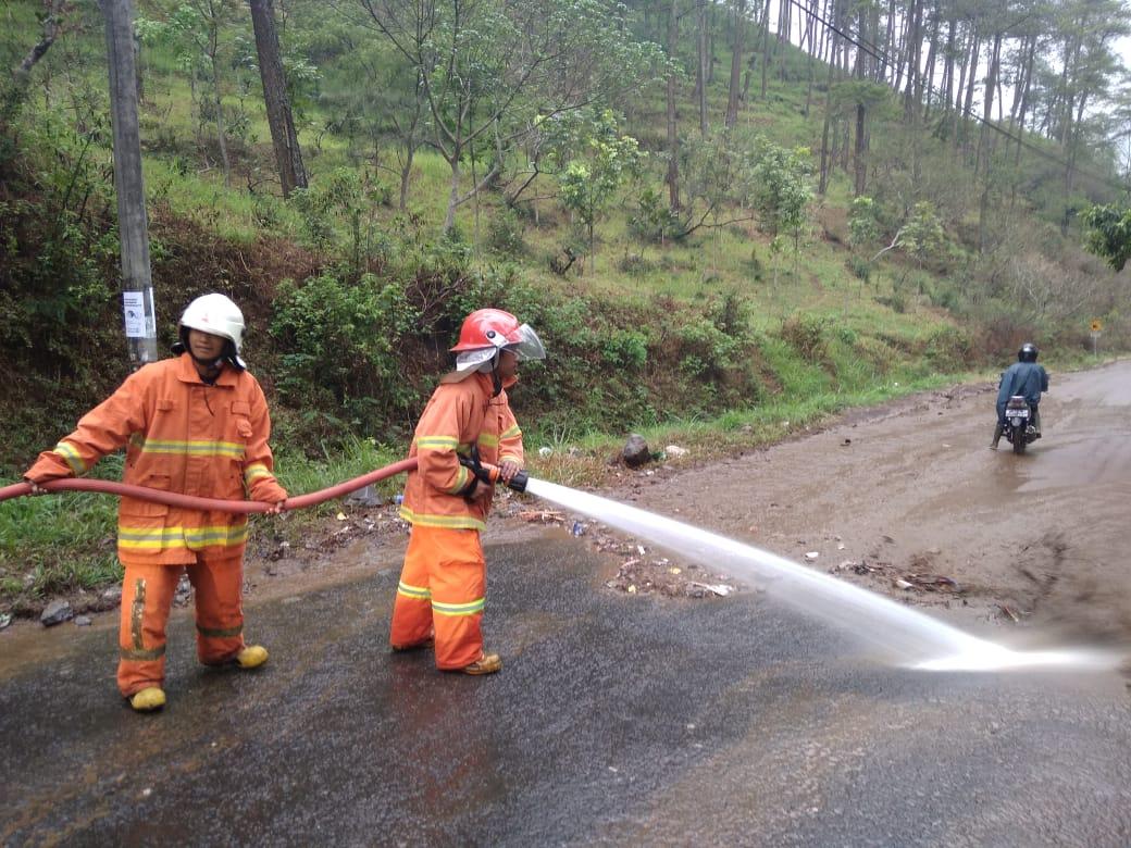Para petugas tengah membersihkan jalan di Kota Batu yang tergenang lumpur dan sampah usai hujan deras. (Foto: BPBD Kota Batu for MalangTIMES)