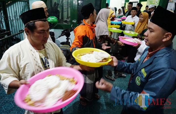 Para santri ketika membagikan nasi liwet kepada seluruh jamaah yang hadir. (Foto: B. Setioko/JatimTIMES)