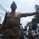 Salah satu petugas mengenakan kostum pejuang sedang mengatur lalu lintas. (eko Arif s/JatimTimes)