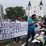 Sejumlah petugas melakukan sosialisasi kegiatan Gebyar Jalan Sehat Sadar Pajak V 2018 yang diselenggarakan BP2D Kota Malang. (Foto: Nurlayla Ratri/MalangTIMES)