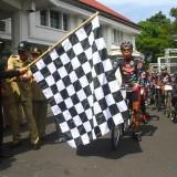Wali Kota Malang Sutiaji mengangkat bendera start pemberangkatan tim Jelajah Sepeda Nusantara 2018 dari halaman Balaikota Malang. (Foto: Nurlayla Ratri/MalangTIMES)