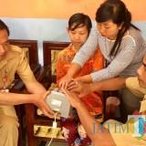 Para petugas saat membantu Yuliani melakukan scan sidik jari di rumahJl Metali Kelurahan Dadaprejo Kecamatan Junrejo, Senin (12/11/2018). (Foto: Irsya Richa/MalangTIMES)