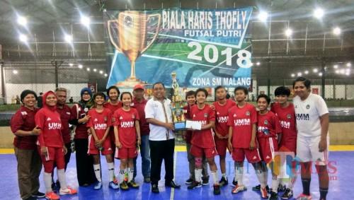 Ketua PSSI Kota Malang Haris Thofly (tengah, baju putih) saat memberikan trofi juara pertama untuk Putri UMM A di turnamen futsal putri Piala Haris Thofly 2018.(Bintang)