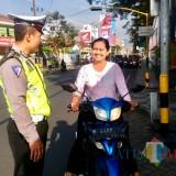 Salah satu petugas Polres Batu menertibkan salah pengendara yang tidak menggunakan helm di Jl Diponegoro. (Foto: istimewa)