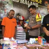 Riyanto (tengah dengan baju tahanan warna oranye), tersangka penipuan yang menyamar menjadi seorang paranormal spesialis pengandaan uang, beserta dua tersangka lain yang diamankan polisi saat sesi rilis di Polres Malang. (Foto : Ashaq Lupito)