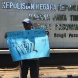 Warga Bulusari menggelar poster di depan Mapolres Pasuruan.