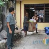 Diawasi oleh juru sita PN Tulungagung, warga keluarkan barang dari rumah Supiadi (foto : Joko Pramono/Jatimtimes)