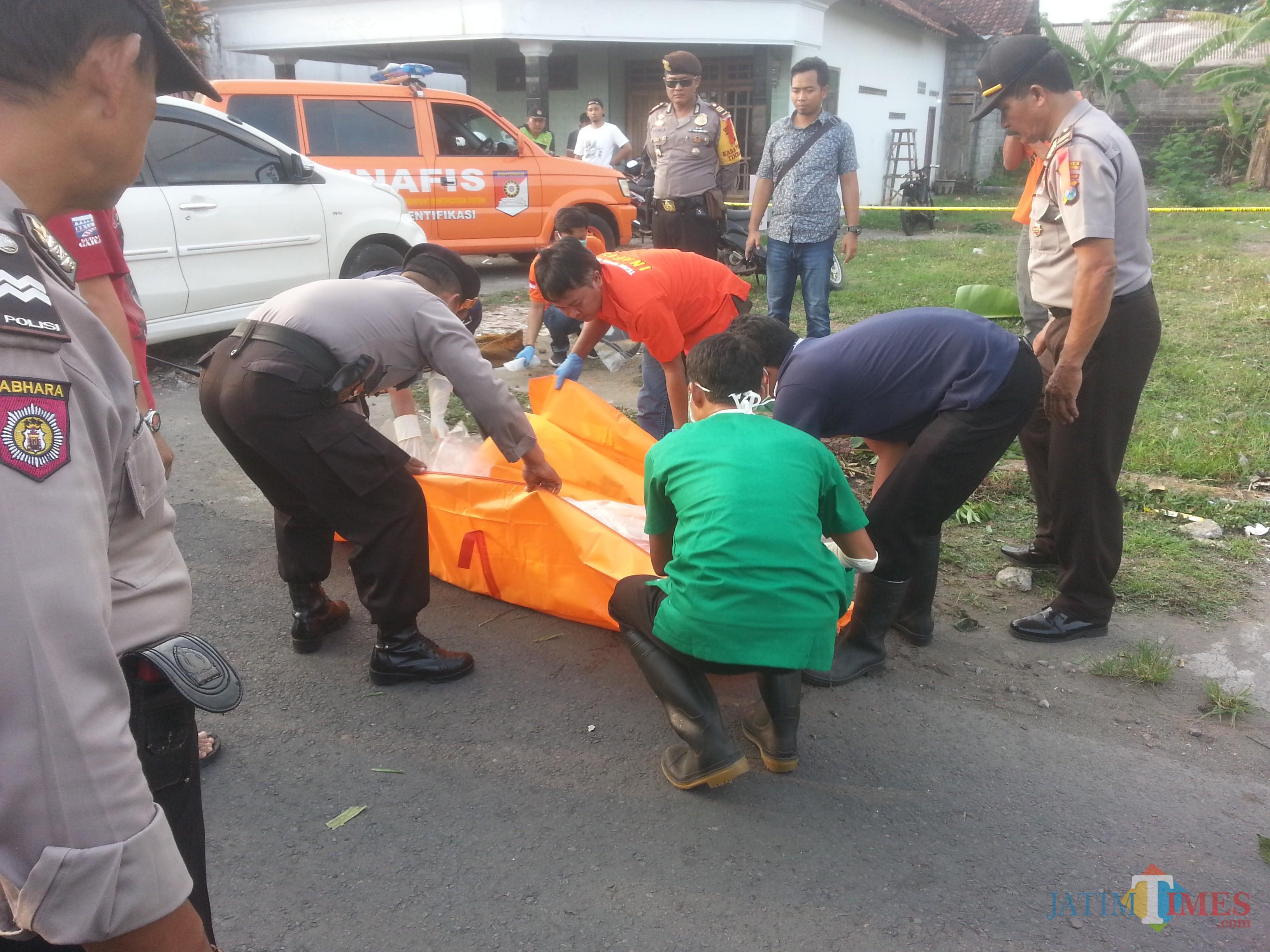 Mayat Barno bersimbah darah di pinggir jalan dengan kondisi luka di pundak dan leher saat dievakuasi.  foto : Joko Pramono/Jatimtimes)