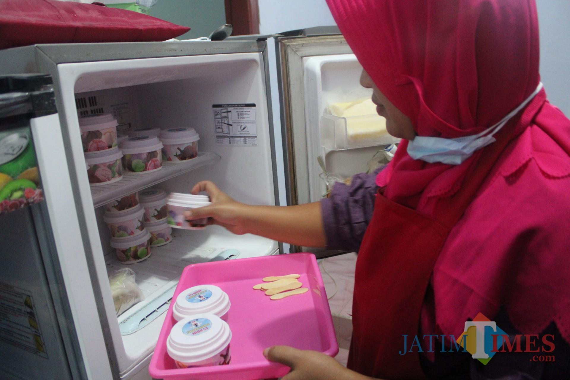 Salah satu warga Desa Galengdowo saat menaruh es krim susu setelah melalui proses pembuatan. (Foto : Adi Rosul / JombangTIMES)