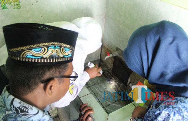 Petugas Puskesmas Perak sedang mendampingi salah satu pelajar SMPN 1 Perak saat mengecek jentik nyamuk di bak air kamar mandi sekolah. (Foto : Adi Rosul / JombangTIMES)