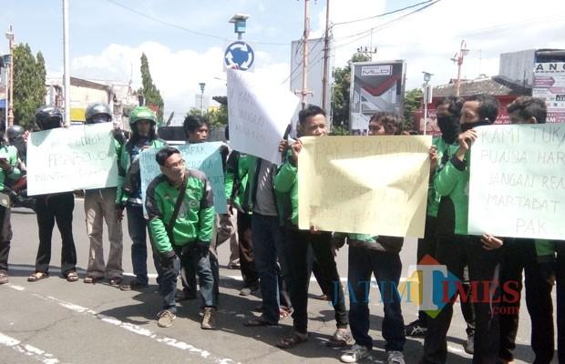 Para Ojol saat menggelar aksi yang digelar di bundaran DPRD usai sholat Jumat (foto : Moh. Ali Makrus / JatimTIMES)