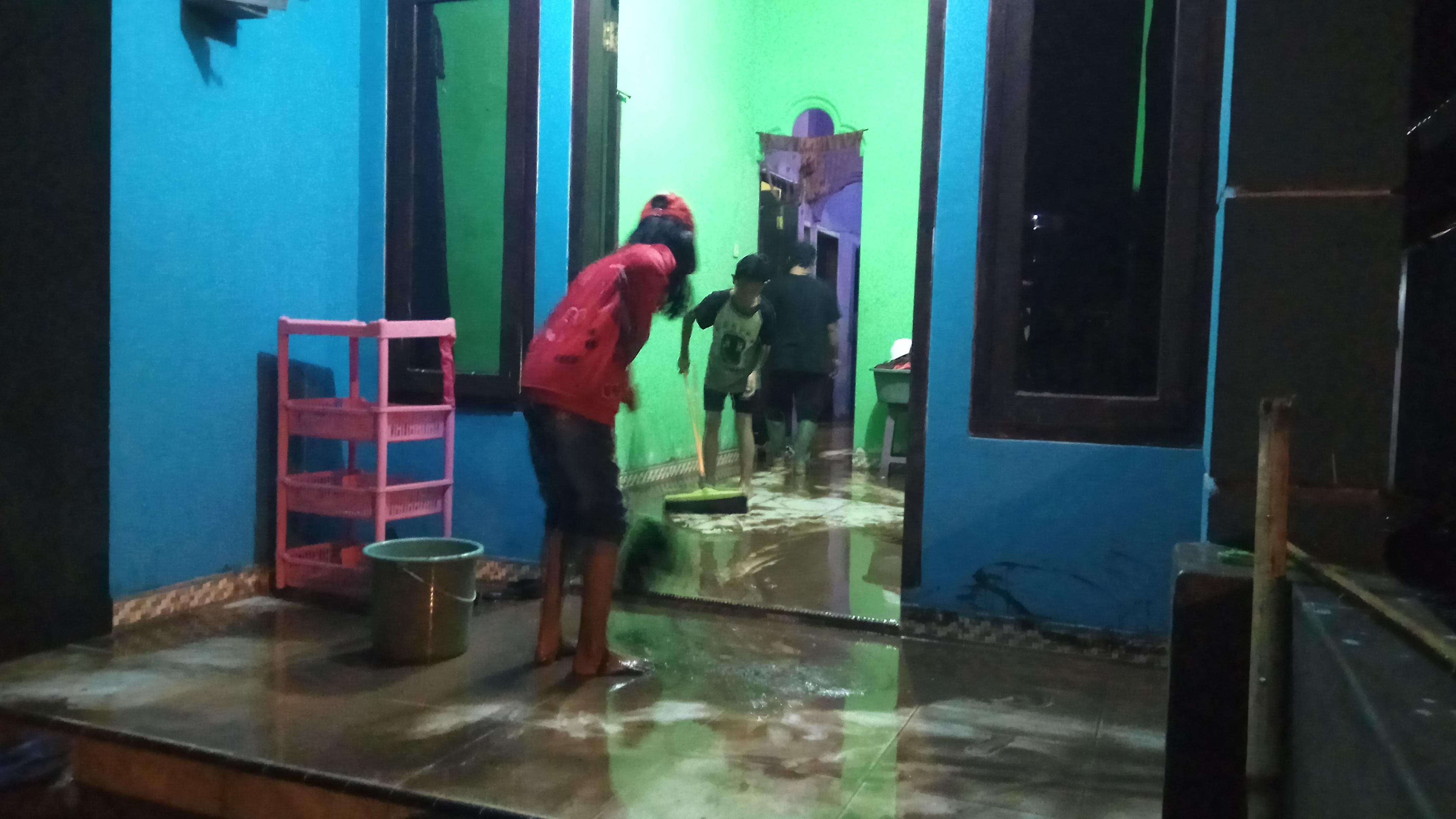 Warga membersihkan lumpur  yang ada di dalam rumah saat luapan air mulai surut.