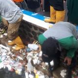 Petugas Satgas DPUPR membersihkan sampah di saluran air kawasan Jalan Galunggung yang mengalami banjir. (DPUPR)