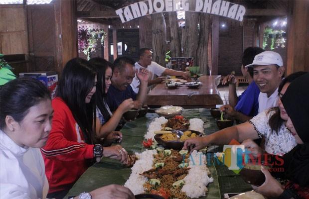 Caption gambar : Sri Hariyati (47), pengunjung asal Kabupaten Malang, saat menikmati Sego Bancakan bersama keluarganya di rumah makan Waroeng Tandjoeng Dhahar. (Foto : Adi Rosul / JombangTIMES)