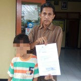 Slamet bersama anaknya menunjukkan pengantar visum usai melapor di Polsek Banyuwangi