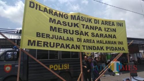 Sebuah spanduk larangan berjualan di sekitar lahan sengketa di Jalan Sudiro, Kota Batu. (Foto: Nurlayla Ratri/MalangTIMES)