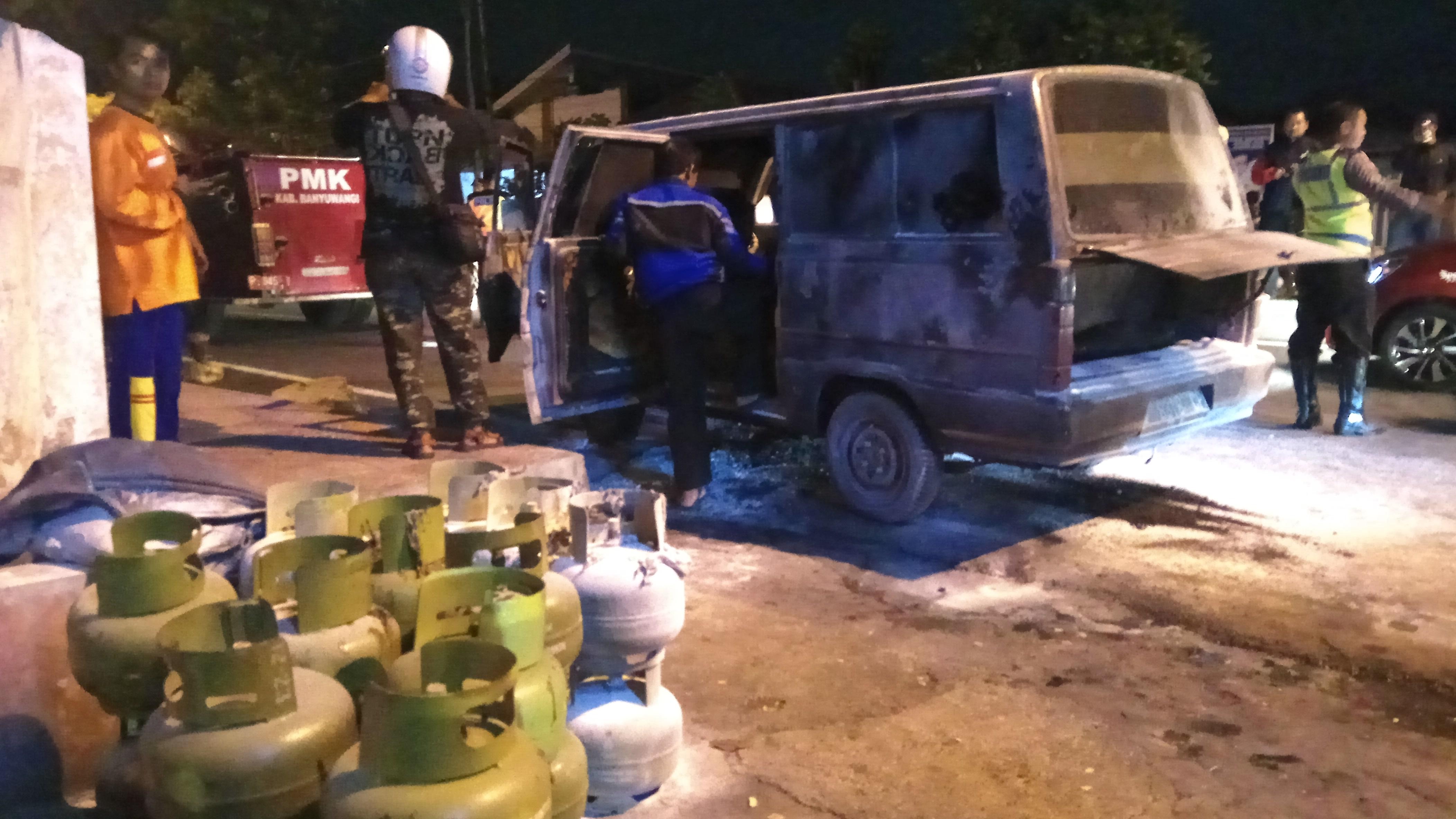 Petugas memeriksa mobil  carry yang terbakar dan tumpukan gas elpiji 3 kg yang sudah dikeluarkan dari mobil