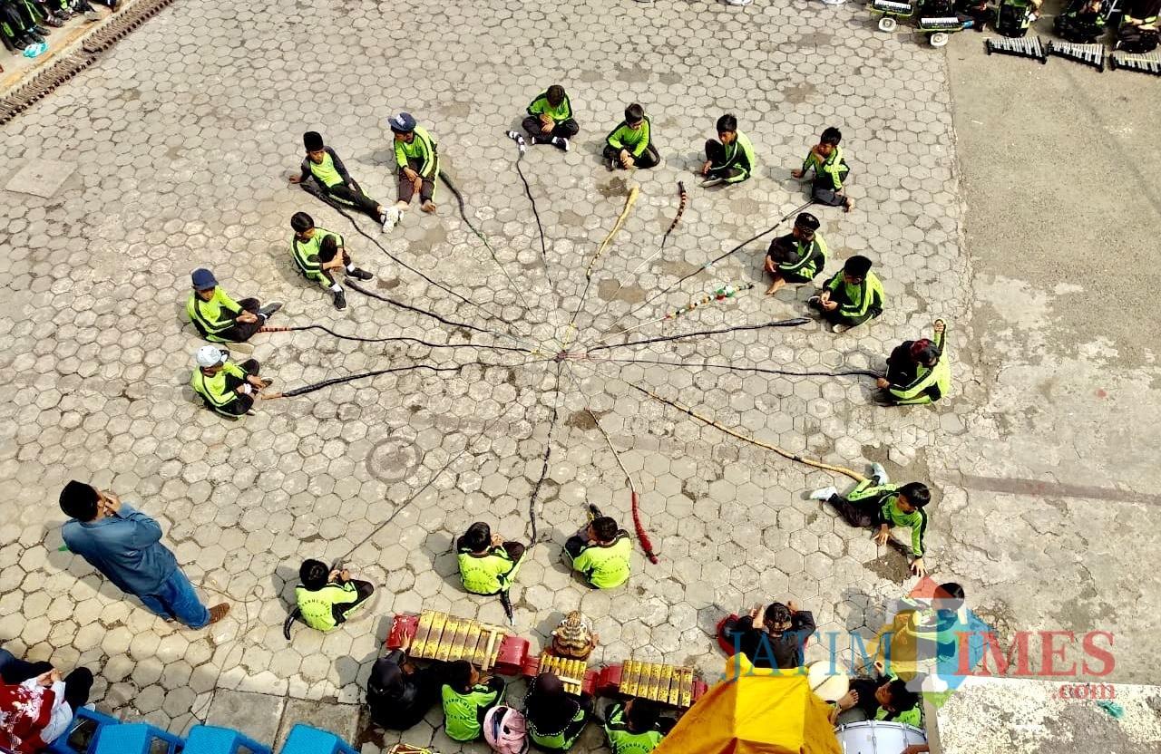 Formasi 19 pelajar denganCemeti Amar Rasuli di halaman sekolahMI Darul Ulum Jl Lahor Desa Pesanggarahan Kecamatan Batu, Sabtu (8/12/2018). (Foto: Irsya Richa/MalangTIMES)