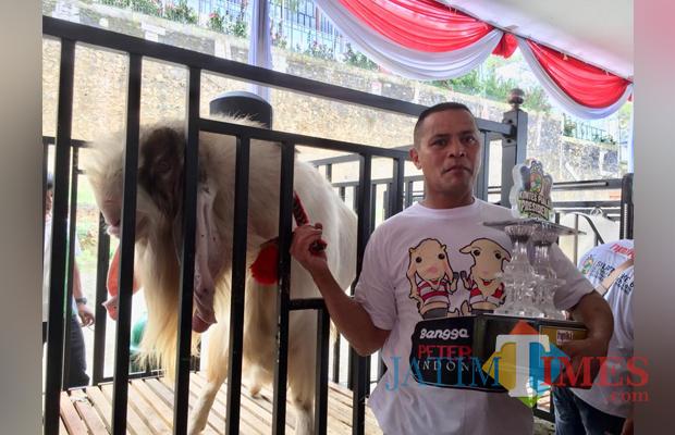 Ade Ridono bersama kambing miliknya bernama Lesno di halaman parkir Jatim Park 2. (Foto: Irsya Richa/MalangTIMES)