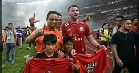Gubernur DKI Jakarta Anies Baswedan (kiri) berpose salam Jak Mania dengan Pemain Persija Jakarta Marko Simic (kanan) beserta supporter usai kemenangan Persija dalam Liga 1 2018 di Stadion Gelora Bunga Karno, Jakarta (Ist).