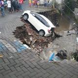 Mobil Jazz putih yang tersangkut usai hujan lebat di Jalan Candi Mendut, Kota Malang Istimewa