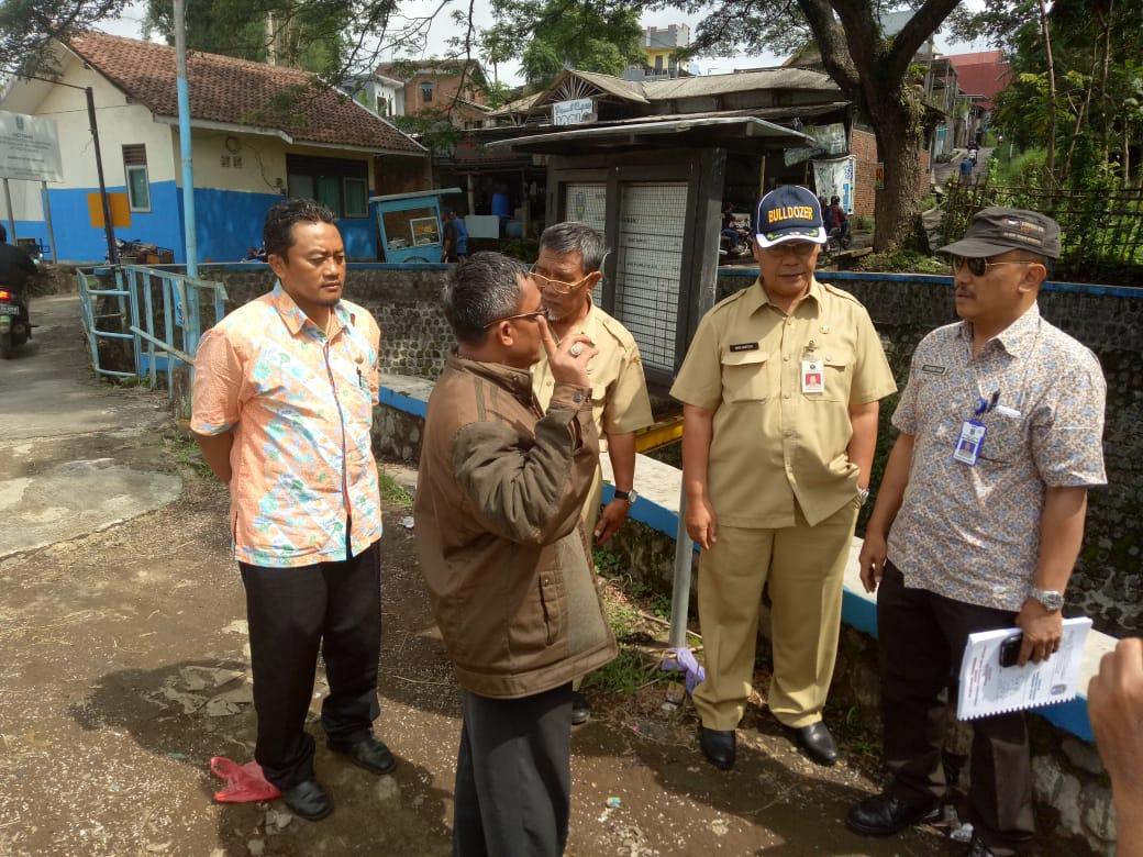 Kepala DPUPR Kota Malang Hadi Santoso (mengenakan topi) saat melakukan pengecekan lokasi pintu air di sungai yang mengarah ke wilayah Kota Malang. (Foto: DPUPR Kota Malang for MalangTIMES)