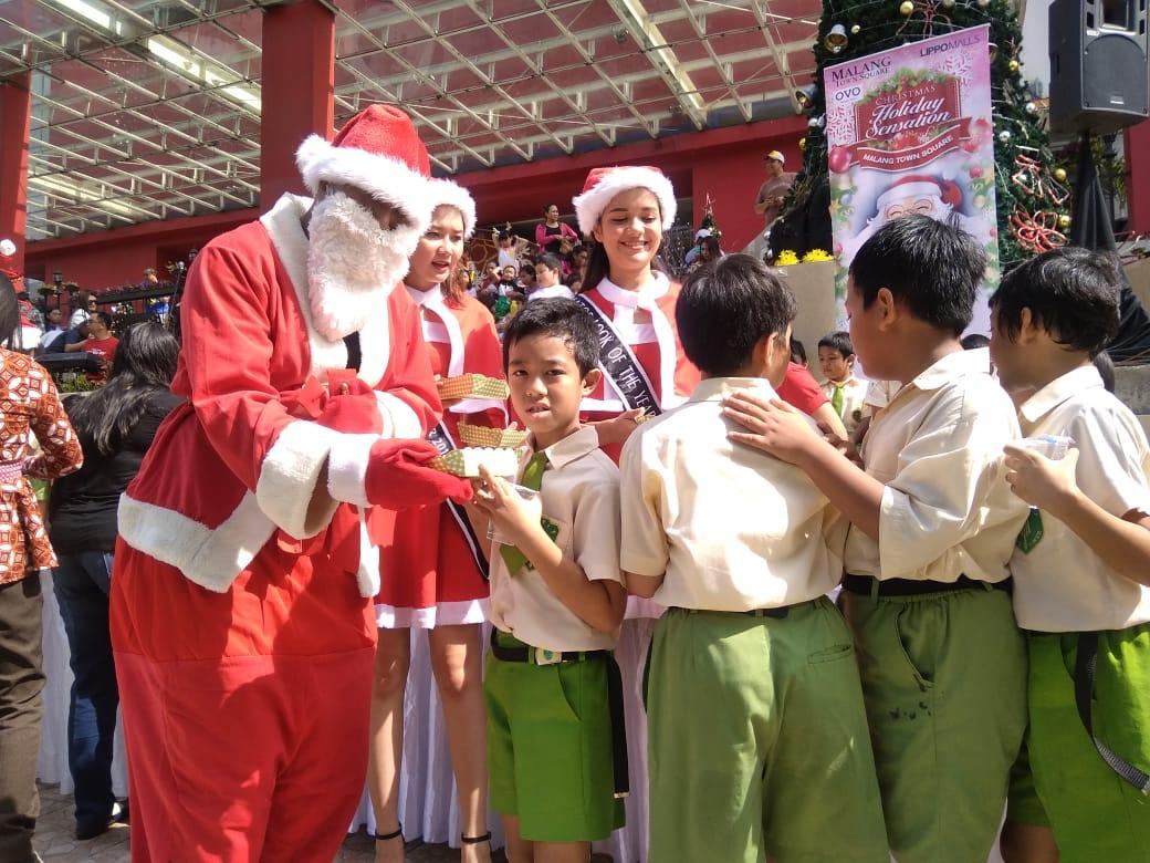 Santa Claus membagikan makanan kepada siswa SD di Matos.