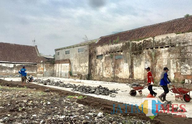 Para pekerja memasang paving di area Selatan GOR Ganesha Alun-Alun Kota Batu. (Foto: Irsya Richa/MalangTIMES)