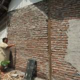 Bu Sumarni menunjukkan dinding tembok yang belum dikuliti (Agus Salam/Jatim Times)