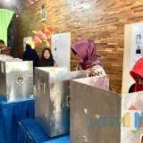Beberapa warga sedang memilih di bilik suara di Kantor Desa Pendem, Minggu (16/12/2018). (Foto: Irsya Richa/MalangTIMES)