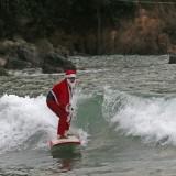 Bawon Santoso dengan dandanan ala Sinterklas berselancar di Pantai Wediawu, Tirtoyudo. Foto : disparbud pemkab malang