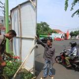 Petugas menurunkan APK Caleg yang menghalangi pandangan pengendara di perempatan jalan KH Mansur (Agus Salam/JatimTIMES)