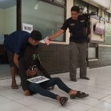 Pelaku memperagakan saat menyeret korban ke dalam rumah (foto : Joko Pramono/Jatim Times)