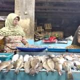 Pedagang ikan di Pasar Besar Kota Malang saat melayani pembeli di tengah melambungnya harga ikan. (Foto: Nurlayla Ratri/MalangTIMES)