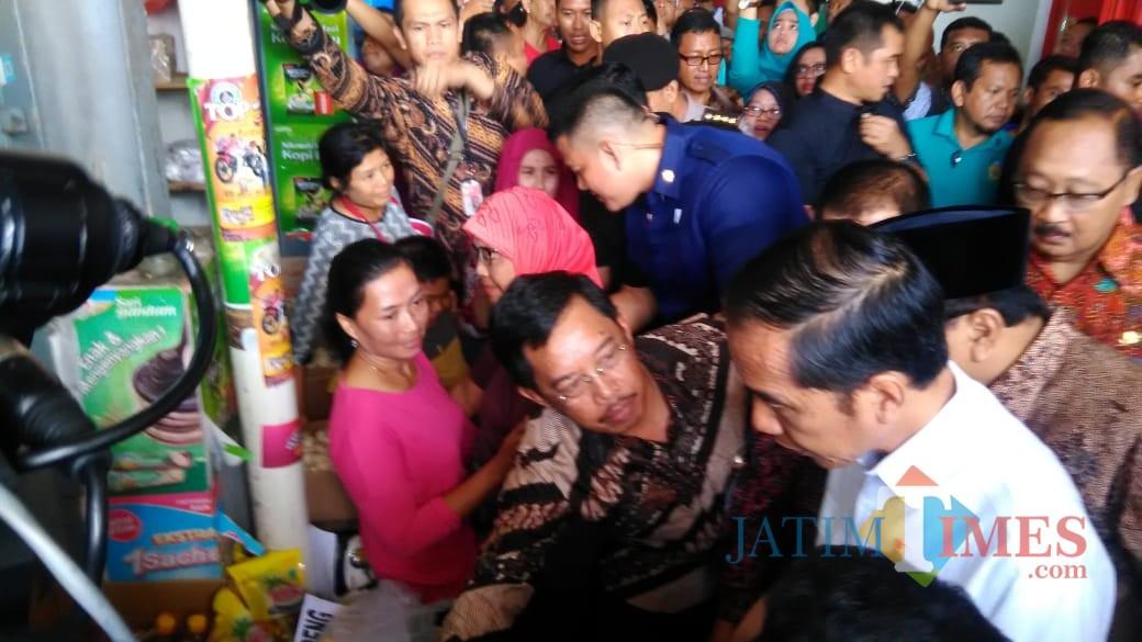 Kadivre Bulog Jatim, Muhammad Hasyim (batik coklat,  berkacamata)  saat tunjukan beras medium ke Presiden Jokowi (foto : Joko Pramono/JatimTIMES)