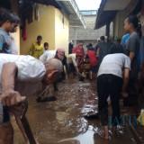 Warga membersihkan material lumpur yang terbawa luapan air sungai