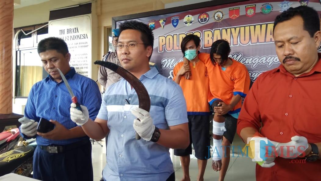 Kasat Reskrim Polres Banyuwangi AKP Panji Prathista Wijaya (tengah) menunjukan celurit yang digunakan tersangka saat beraksi, Selasa (8/1/2019) (Foto : Muhammad Hujaini/BanyuwangiTIMES)